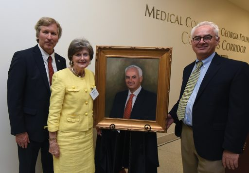 Dean David Hess, artist Sandra T. Colquitt and Dr. Peter F. Buckley, MCG's 26th dean, unveil Buckley's portrait at Alumni Weekend.