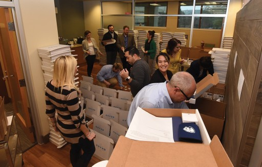 Photo by Phil Jones. Communications and Marketing staff assemble 1,000 brand starter kits for launch day delivery.