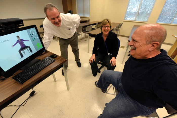 Drs. Paul York and Charlotte Chatto watch as Joe Kelley exercise using the motion-capture software.
