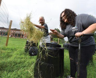 Dr. Donna Wear and Bryauna Barrera (BS '18) sort through compost barrels. Photo by Phil Jones