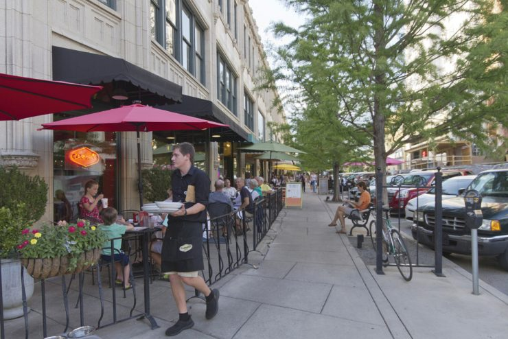 ASHEVILLE, NORTH CAROLINA - JUNE 29, 2017: A busy downtown Asheville street lined with cafes, restaurants, benches and tourists on a summer afternoon
