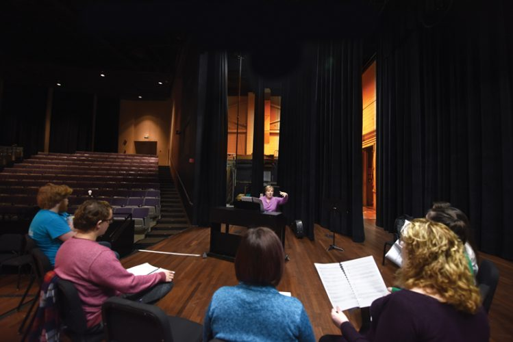 Associate music director and voice coach Pam McCorkle works with the cast on the stage of the Maxwell Theatre.