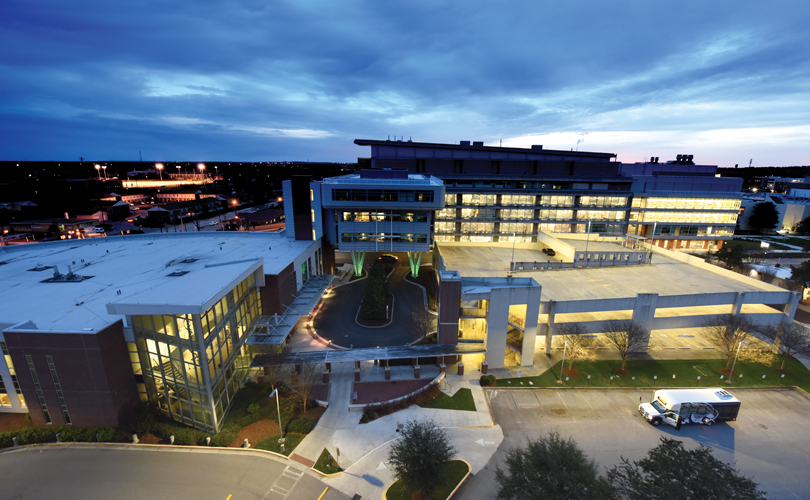 The Georgia Cancer Center at dusk, with the Ribbons of Hope sculpture hanging in the atrium (near left). Photo By Phil Jones | Nikon d810, 14.0 mm lens, 1/20 sec@f/4.5, ISO 1600