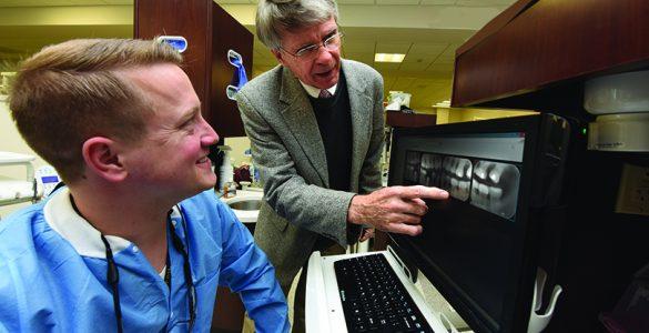 Dentist pointing at x-ray with a man at a keyboard