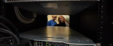 Two women looking through window in server farm