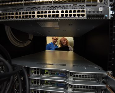 Two women looking through window in server farm