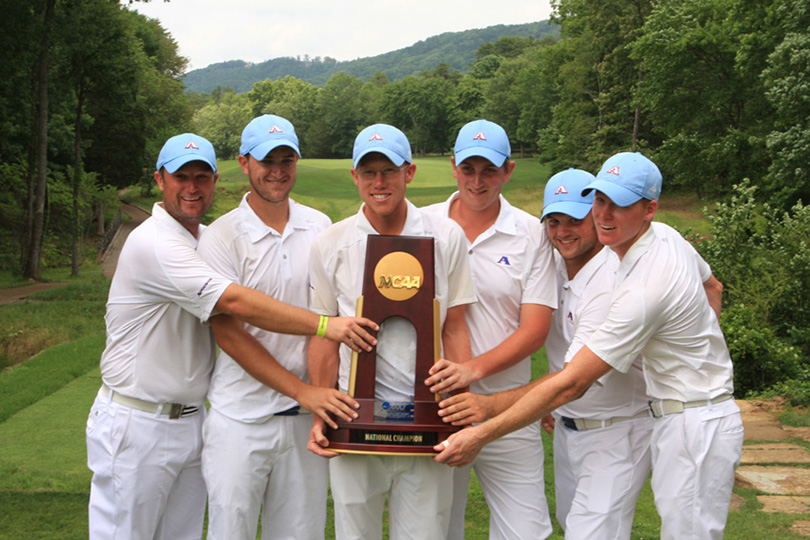 golfers holding trophy