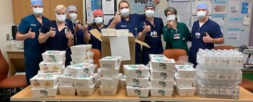 masked medical staff receiving food donation