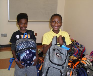 kids smiling with backpacks