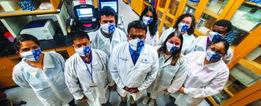 masked researchers in lab