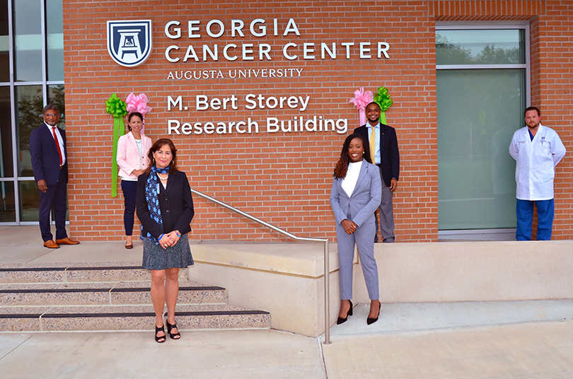 group smiling in front of building