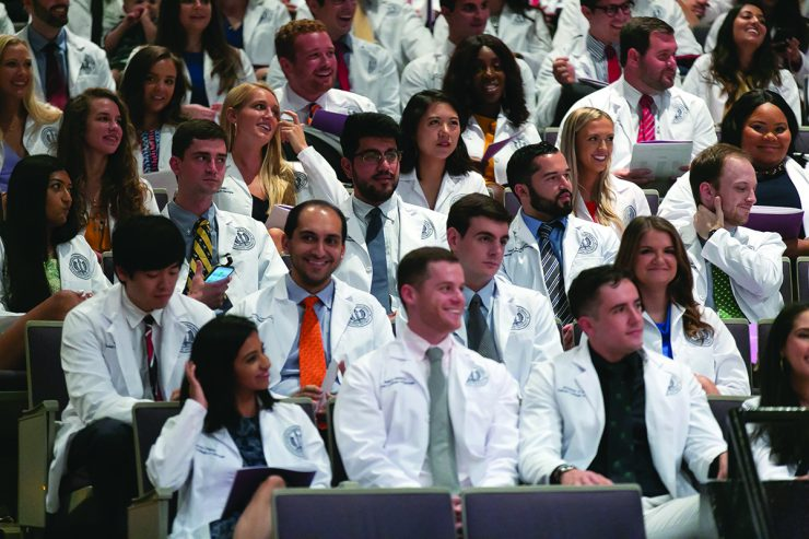 Large group of students smiling during white coat ceremony