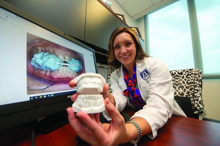 Woman showing model of teeth - Dr.Jacqueline Delash
