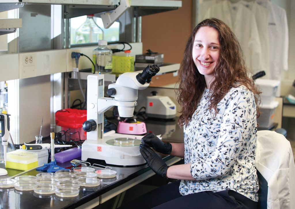 woman sitting in front of microscope turned to smile at camera