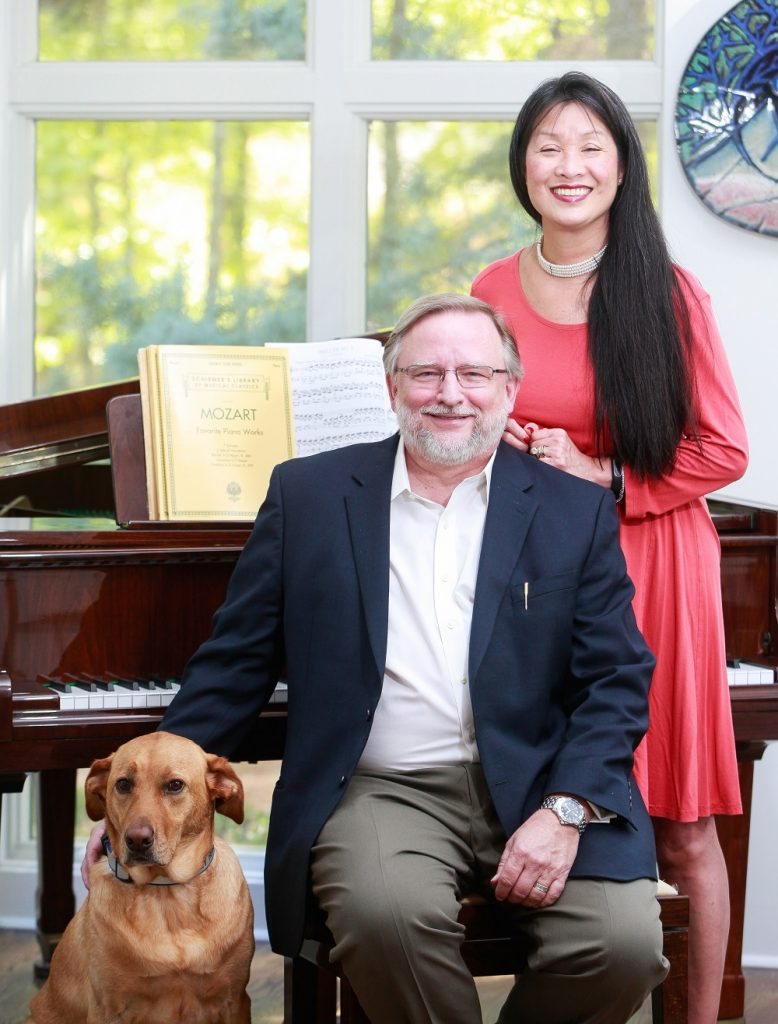 smiling man, smiling woman and dog pose for picture