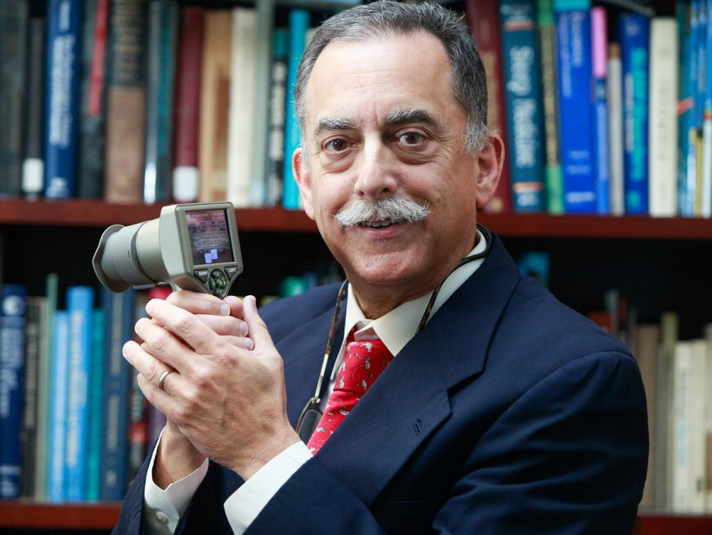 man smiling with pupillometer